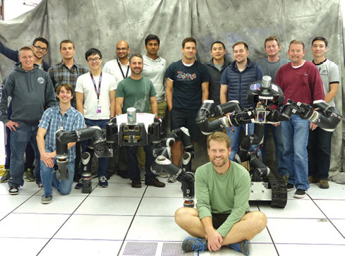 Robotics researchers at NASA's Jet Propulsion Laboratory pose with robots RoboSimian and Surrogate. Image courtesy of JPL-Caltech.